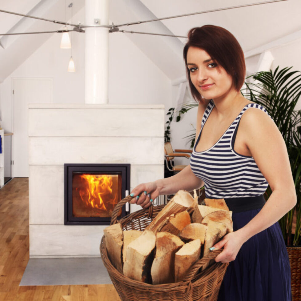 lady with firewood in front of a fireplace
